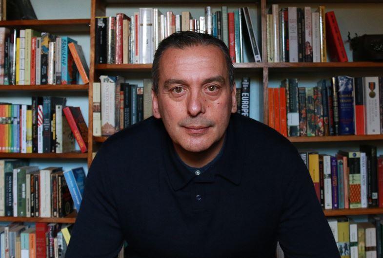 Christos Tsiolkas infront of a bookshelf.